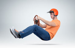 Funny man in helmet car driver with wooden steering wheel, auto concept. On background Stock Photos