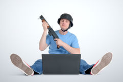 Funny man in helmet with shotgun sitting on the floor in front of a laptop Stock Photography