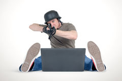 Funny man in helmet with shotgun sitting on the floor in front of a laptop. Armchair warriors concept Royalty Free Stock Images