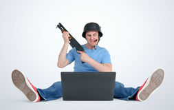 Funny man in helmet with shotgun sitting on the floor in front of a laptop. Stock Images