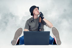 Funny man in helmet with shotgun sitting on the floor in front of a laptop smoke Stock Photography