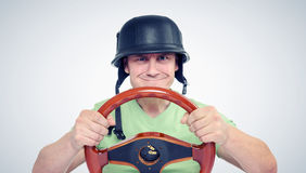 Funny man in helmet with steering wheel, car drive concept.  Stock Photo