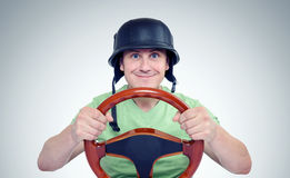 Funny man in helmet with steering wheel, car drive concept Royalty Free Stock Images