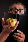 Funny Man hides behind big sleek leather book. Old Man with beard and big nerd glasses showing apples in hand hides behind the black leather book funny Stock Photos