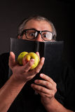 Funny Man hides behind big sleek leather book. Old Man with beard and big nerd glasses showing apples in hand hides behind the black leather book funny Royalty Free Stock Photos