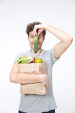 Funny man holding a bag full of groceries. And holding cucumber Royalty Free Stock Photography