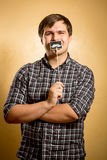 Funny man holding fake mustache on stick at mouth Stock Photo