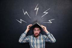 Funny man holding laptop above head over background of chalkboard. Funny shocked young man holding laptop above his head immitating roof and hiding from Stock Images