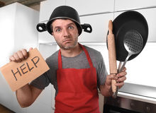 Funny man holding pan with pot on head in apron at kitchen asking for help Stock Photos