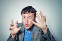 Funny man in jacket grimaces and frightens stock photo