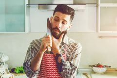 Funny man joking at kitchen with knife and beard Royalty Free Stock Photos
