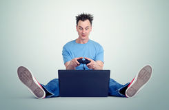 Funny man with a joystick sits on the floor in front of a laptop. Gamer plays. Royalty Free Stock Image
