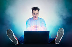 Funny man with joystick sits on the floor in front of a laptop. Gamer plays. Royalty Free Stock Image