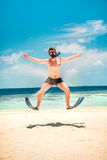 Funny man jumping in flippers and mask. Holiday vacation on a tropical beach at Maldives Islands Stock Images