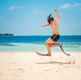 Funny man jumping in flippers and mask. Holiday vacation on a tropical beach at Maldives Islands Royalty Free Stock Images