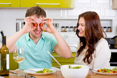 Funny man keeping cherry tomatoes on his eyes with wife Royalty Free Stock Photos