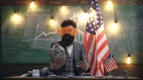 Funny man. Man in large glasses hugs bank with money. USA flag background. Economy and finance. Patriotism and freedom. Independence day of usa. Travel stock video