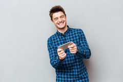 Funny man laughing while playing with smartphone royalty free stock images