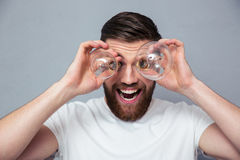 Funny man looking at camera through bulb Royalty Free Stock Photos