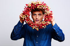 Funny man looking through a wreath Royalty Free Stock Image