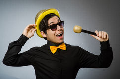 The funny man with mic in karaoke concept. Funny man with mic in karaoke concept Stock Photo