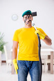 The funny man in military style cleaning the house Royalty Free Stock Images