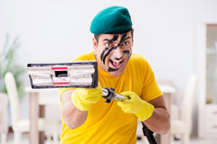 The funny man in military style cleaning the house Royalty Free Stock Image