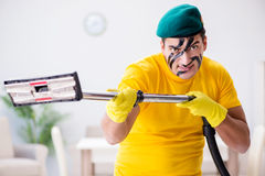 The funny man in military style cleaning the house Royalty Free Stock Photography