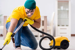 The funny man in military style cleaning the house Stock Photos