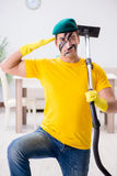 The funny man in military style cleaning the house Royalty Free Stock Photo