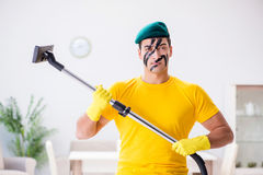The funny man in military style cleaning the house Stock Image