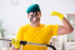 The funny man in military style cleaning the house Stock Photography
