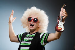 Funny man. With miniature guitar Stock Image