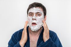 Funny man with natural white cream mask on his face stock photography