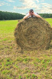 Funny man on nature. Funny man lie on bale in field Stock Photography