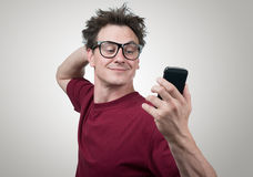 Funny man photographing himself on a smartphone. On background Stock Image