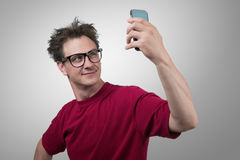 Funny man photographing himself on a smartphone Royalty Free Stock Image