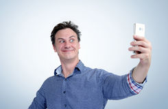 Funny man photographing himself on a smartphone Royalty Free Stock Photo