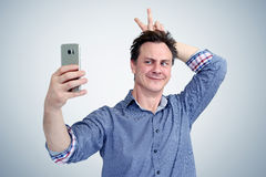 Funny man photographing himself on a smartphone. Be fashionable concept Stock Image