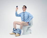 Funny man photographing himself in the toilet Royalty Free Stock Photography