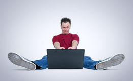 Funny man playing games sitting on the floor in front of a laptop Royalty Free Stock Images