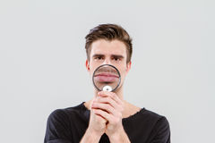 Funny man playing tricks using magnifying glass Royalty Free Stock Photography