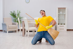 The funny man playing virtual guitar with broom. Funny man playing virtual guitar with broom Stock Photo