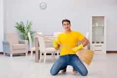 The funny man playing virtual guitar with broom. Funny man playing virtual guitar with broom Royalty Free Stock Photography