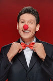 Funny man. Portrait of cheerful man with a clown nose touching h. Is bow tie and looking at camera Royalty Free Stock Photography