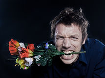 Funny Man Portrait offering flowers. Studio portrait on black background of a funny expressive caucasian man offering flowers anger Stock Photos
