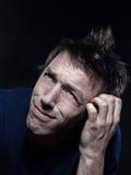 Funny Man Portrait pucker hesitant. Studio portrait on black background of a funny expressive caucasian man puckering hesitant Stock Photography