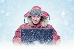 Funny man programmer in red winter clothes with laptop, cold, snow, blizzard Royalty Free Stock Photo
