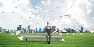 Young businessman or student studying the science and paper planes flying around Royalty Free Stock Photo