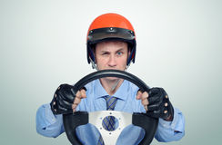 Funny man in a red helmet with steering wheel, car driver concept.  Royalty Free Stock Image